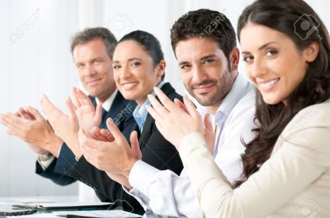 8590040-satisfied-proud-business-team-clapping-hands-and-looking-at-camera-in-a-modern-office-stock-photo